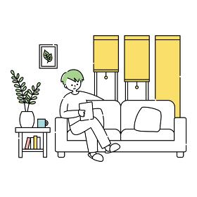 ソファーでタブレットを見ながらくつろぐ男性