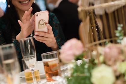 披露宴でスマホを見る女性