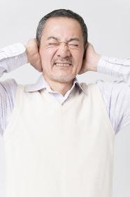 耳を塞ぐシニア男性