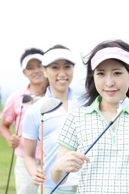 ゴルフクラブを持って微笑む男女