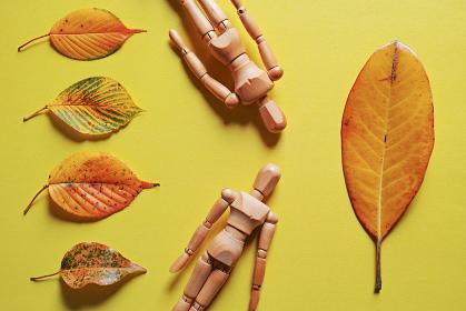 黄色い紙の上に置いた5枚の落ち葉と二つの木製人形。秋のイメージ。