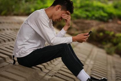 スマートフォンを見て頭を抱える男性