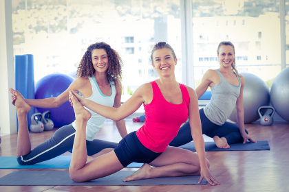 Women doing pigeon pose with one hand right leg grab