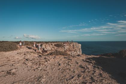 Hikers enjoying view over ocean in summer in Sagres, Portugal