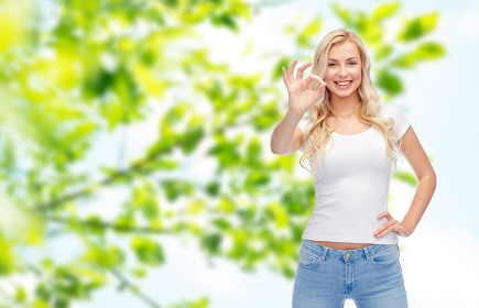 happy young woman in white t-shirt showing ok sign