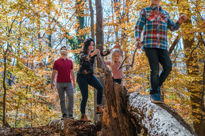 Family balancing on logs walking together in forest
