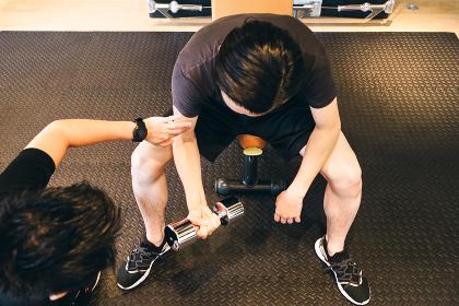 ダンベルを持ち上腕二頭筋を鍛える男性