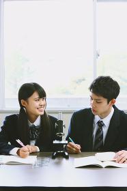 顕微鏡で実験している高校生