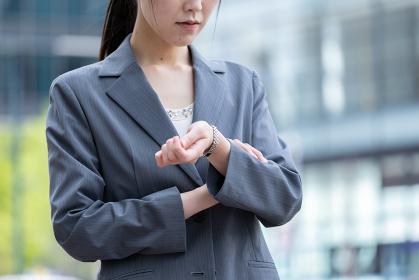 オフィス街で腕時計で時間を確認する若いビジネスウーマン