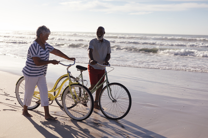 Happy senior african american couple with bicycles walking together on the beach. travel vacation retirement lifestyle concept