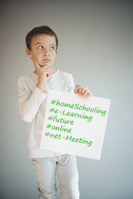boy holding white sign with the words homeschooling and more during corona crisis