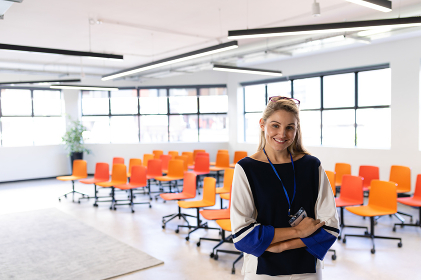Front view of a Caucasian woman with long blond hair, wearing smart clothes, standing in an empty modern meeting room, smiling and looking straight into a camera.