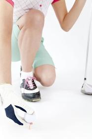 ゴルフボールをセットする女性の手元