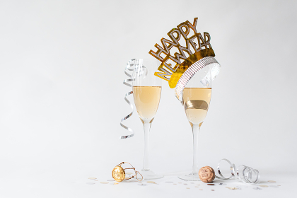 Glasses of champagne and Happy New Year hat on white background.