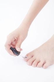 足にネイルを塗る女性の手元