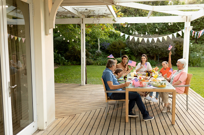 Front view of a multi-generation Caucasian family sitting outside on a deck at a dinner table set for a meal, celebrating and waving US flags. Family enjoying time at home, lifestyle concept