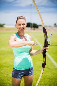 Portrait of female athlete practicing archery