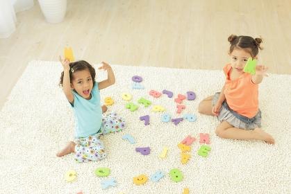 アルファベットのパズルで遊ぶ女の子たち