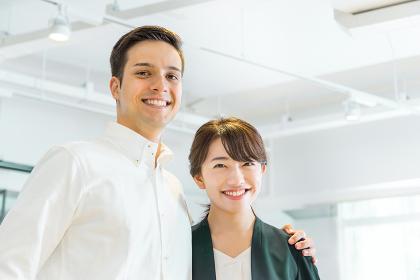 笑顔で肩を組む男性と女性(人種の違う人々)