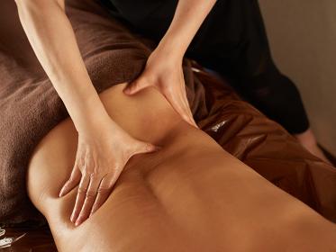 腰のマッサージを受けるアジア人男性