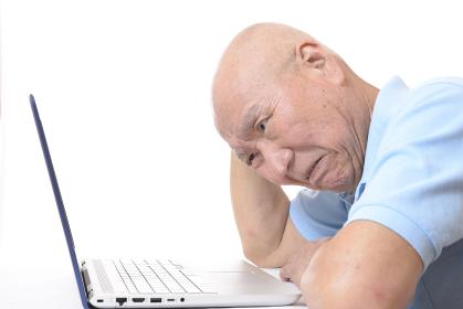 ノートパソコンを操作するシニア男性
