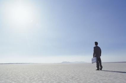 砂漠を歩くビジネスマン