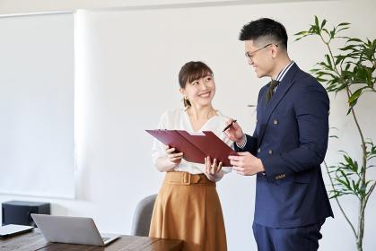 アジア人の先輩ビジネスマンに資料のチェックをお願いするビジネスウーマン