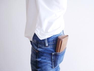 お財布をデニムのポケットに入れている女性