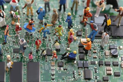パソコンの基盤の上にいる人間のミニチュア人形のジオラマ風景