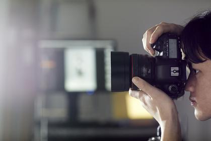 一眼レフカメラで撮影する日本人男性