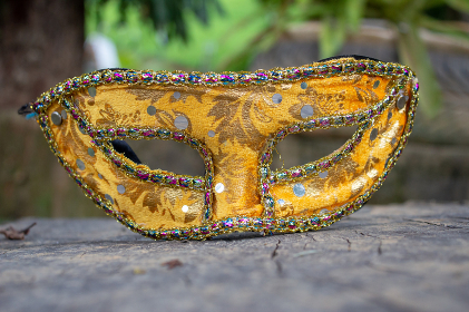 Carnival mask from Brazil, resting on a wooden board