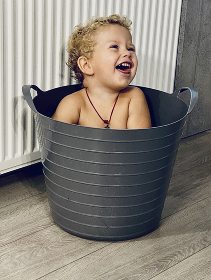 the boy smiles and sits in a basin, free seat