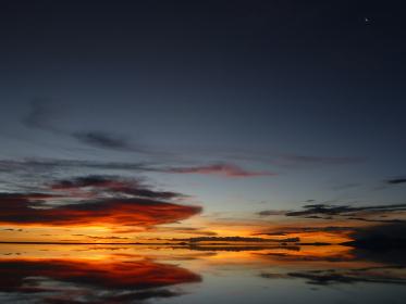 ボリビアのウユニ塩湖にて水面に鏡のように反射するオレンジ色の夕日