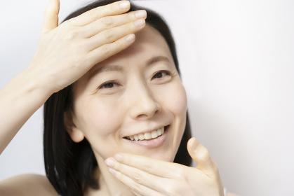 顔を触る日本人女性(40-50代のイメージ)