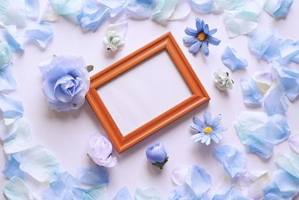 白背景に青色の造花と花びら。中央に斜めの木製フォトフレームと白いコピースペース。平置きの俯瞰撮影。
