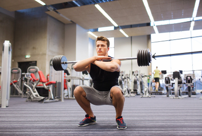 young man flexing muscles with barbell in gym