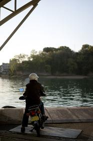 オートバイに乗り渡船を待つ人