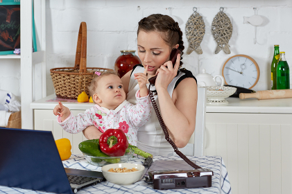Mother with notebook and baby in kitchen. Isolation period, quarantine, social distancing. Remote education or remote work
