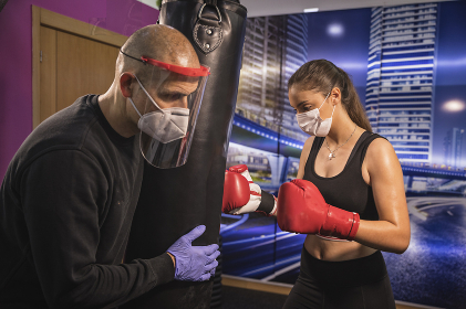 Training with personal trainer and covid19 virus protection masks
