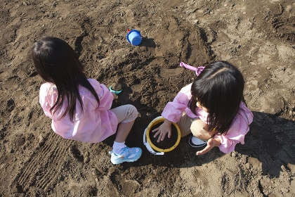 砂場で遊ぶ幼稚園女児2人