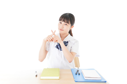 バツを示す制服姿の女子学生