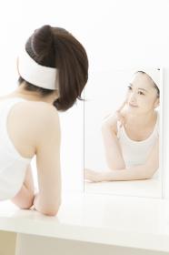 鏡で肌を見る女性