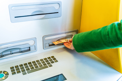 woman dressed in green coat taking out a 50 euro bill from an ATM