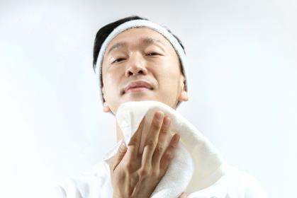 タオルで顔をふく日本人の中年男性