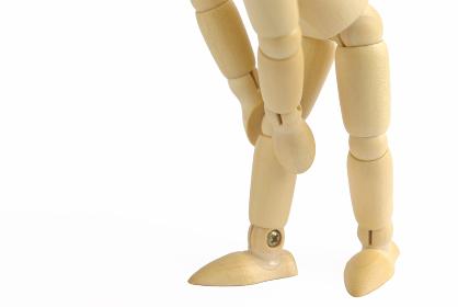 膝を押さえるポーズをした横向きの木製のモデル人形のアップ