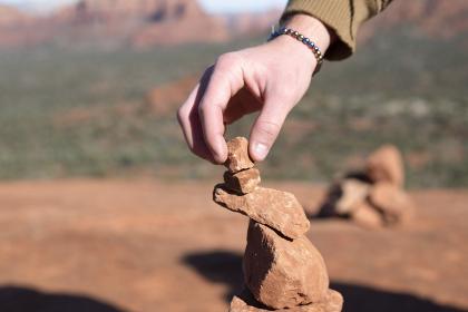 hand balancing red stone on a rock tower in Sedona Arizona