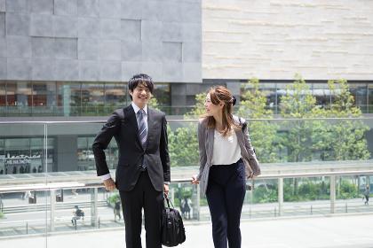 オフィス街で談笑する男女(ビジネスイメージ)