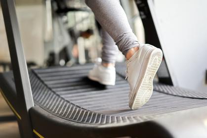ランニングマシンで走るアジア人女性の足元
