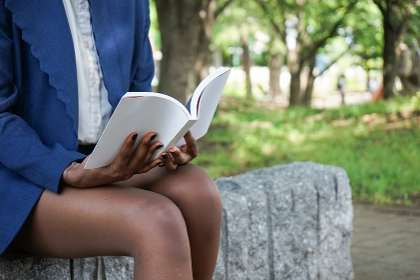 公園で読書をする黒人女性