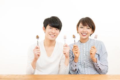 スプーンとフォークを持つ若いカップル